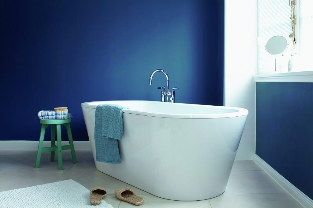 Badezimmer mit Wandfarbe in Blau, freistehender Badewanne und Hocker in Grün / Türkis / Petrol